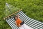 Thumbnail Senior woman with netbook and headset lying in a hammock