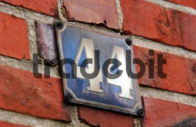 Attendance in the parants house: Detail and memories. House number 44 on enamel sign on bricked brick wall.