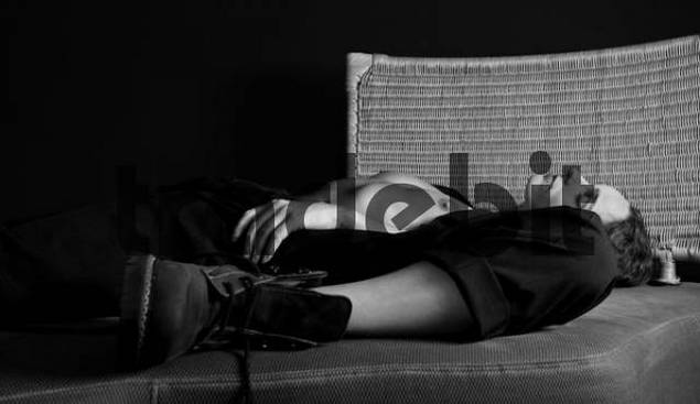 Semi-nude woman lying on a sofa and daydreaming in black-and-white
