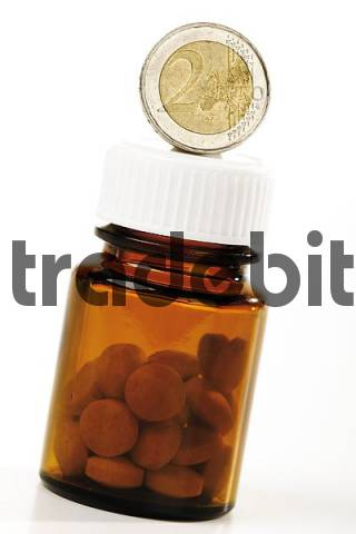 Euro coin and pill bottle: symbol for rising medical costs